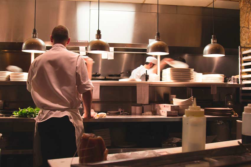 Cocina de un restaurante en la que los cocineros están trabajando.