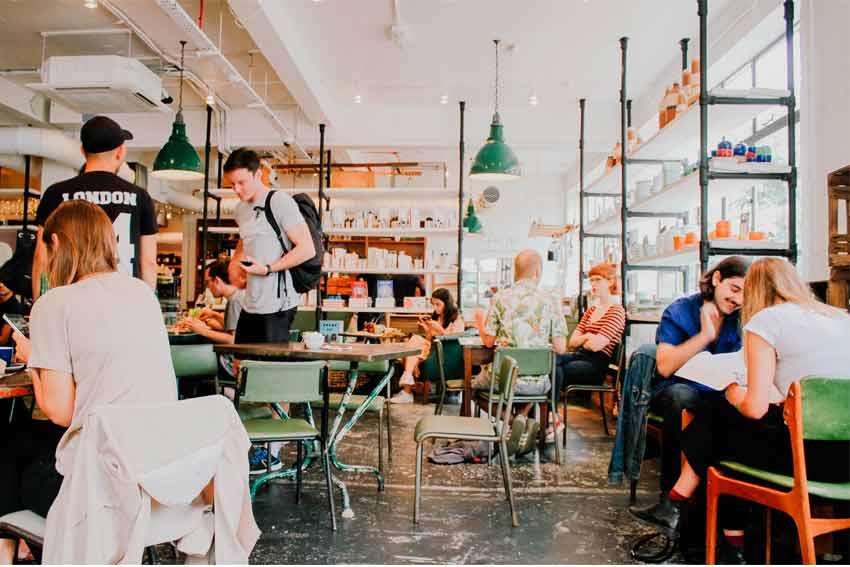 Sala de una cafetería con clientes.