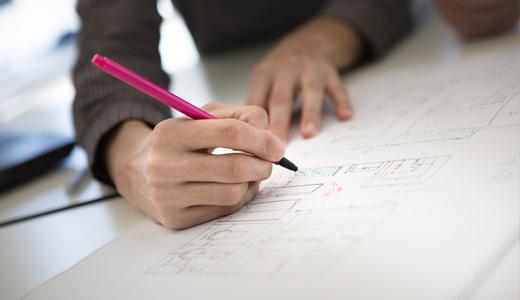 Loli Pardo realizando anotaciones sobre un plano de un proyecto de Interiorismo Comercial.