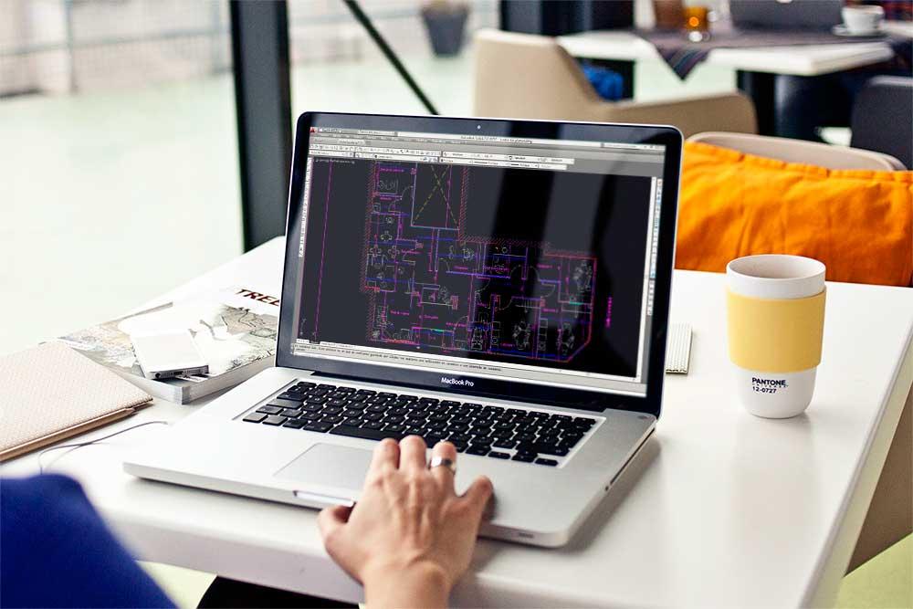 Persona trabajando en una cafetería con Autocad en un laptop desarrollando una distribución en planta de un Restaurante.