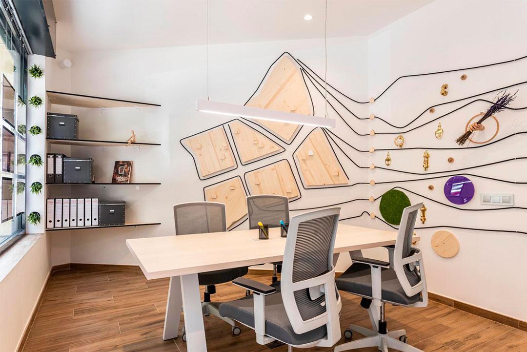 Zona de trabajo con detalles de la decoración en la pared de la empresa Soluciones Inmobiliaria MAPROFIT de Madrid.